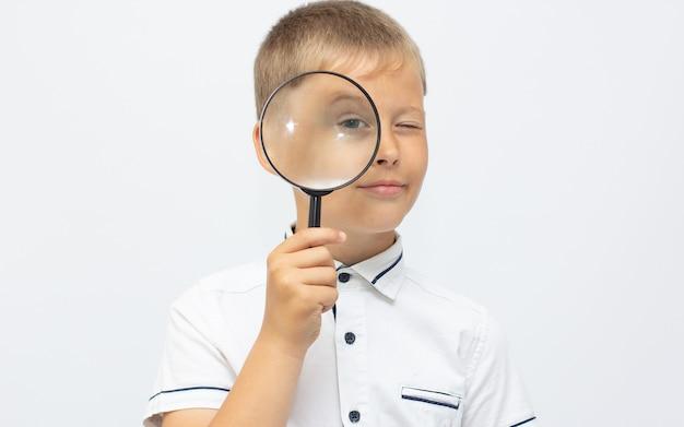Gros plan d'un bel enfant regardant à travers une boucle de loupe sur blanc