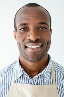 Gros plan d'un bel homme afro-américain positif souriant en se tenant debout contre le mur blanc