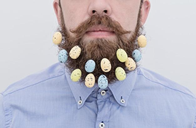 Gros plan de bel homme barbu avec des oeufs de pâques