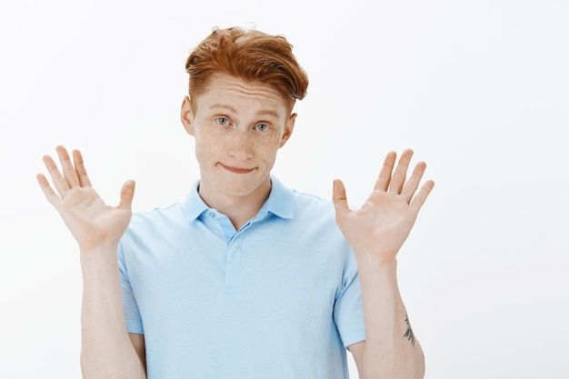 Gros plan d'un bel homme rousse levant les mains en signe de reddition, ne sachant rien
