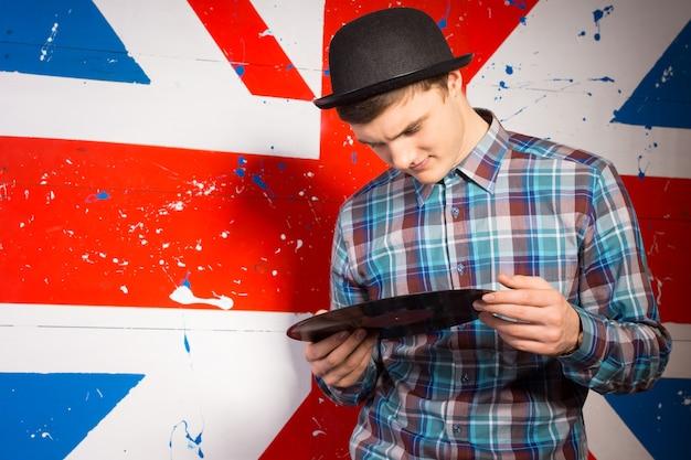 Gros plan bel homme en tenue tendance tenant une plaque de disque vinyle devant l'impression du drapeau britannique