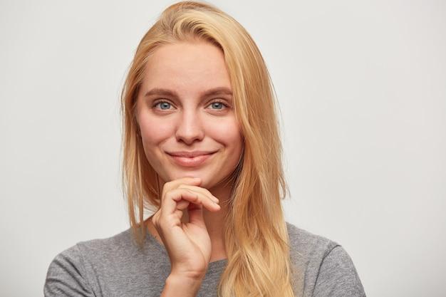 Gros plan de la belle belle jeune femme blonde aux yeux bleus flirter tendrement souriant