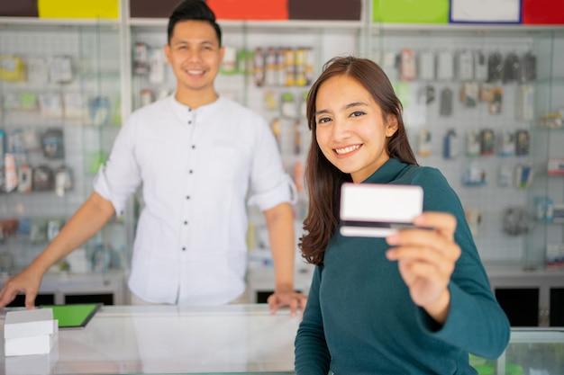 Gros plan d'une belle cliente montre une carte de crédit pour le paiement sans espèces