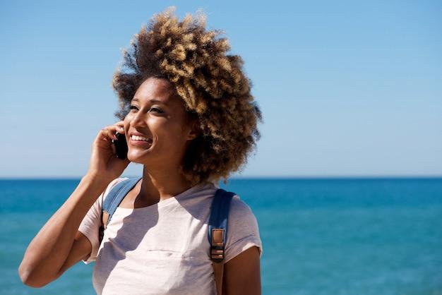 Gros plan belle femme africaine parlant au téléphone portable au bord de la mer