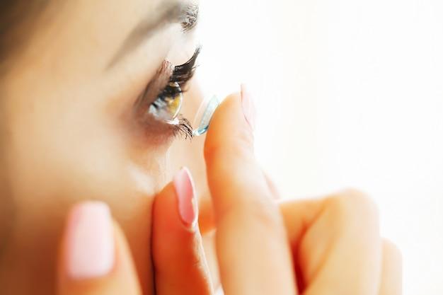 Gros plan, de, belle femme, appliquer, lentille oeil, dans, oeil