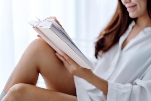 Gros plan d'une belle femme asiatique lecture livre dans une chambre à la maison