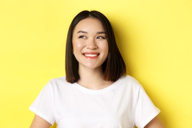 Gros plan d'une belle femme asiatique en t-shirt blanc, souriant et regardant à gauche avec un visage heureux
