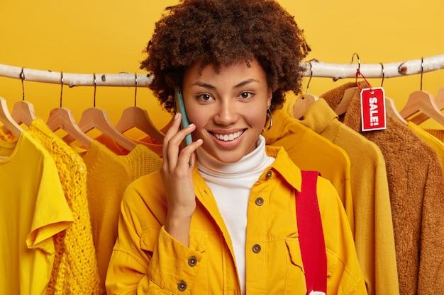 Gros plan d'une belle femme aux cheveux bouclés fait un appel téléphonique, sourit largement, vêtue d'une veste jaune