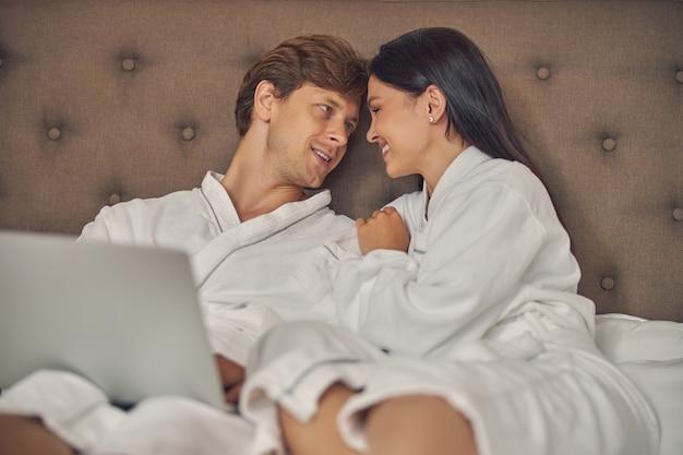 Gros plan belle femme et bel homme se détendre sur le lit et se regarder
