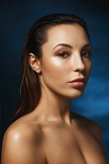 Gros plan d'une belle femme avec du maquillage de mode, regardant droit.