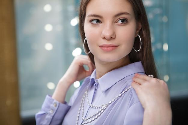 Gros plan d'une belle femme essayant des bijoux à la boutique
