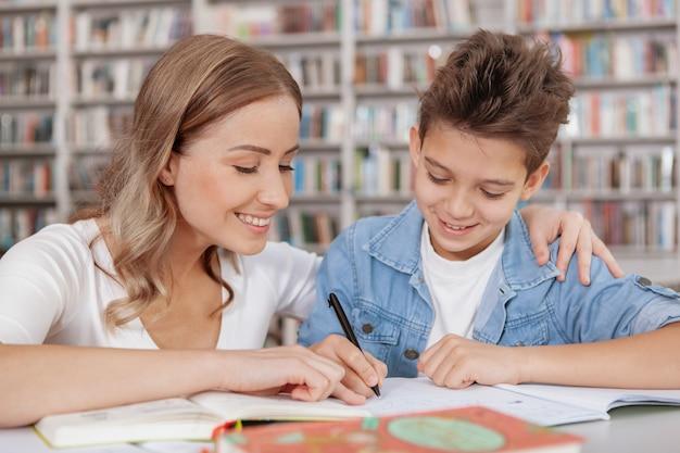 Gros plan d'une belle femme joyeuse aidant son fils avec l'affectation de l'école à la bibliothèque