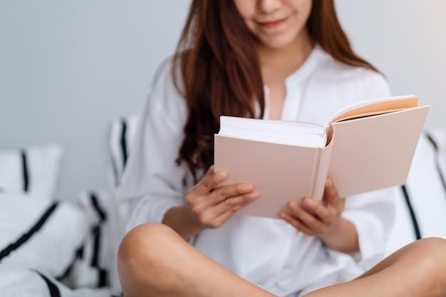 Gros plan d'une belle femme lisant un livre dans un lit confortable blanc à la maison