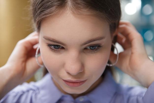 Gros plan d'une belle femme portant des boucles d'oreilles, touchant ses cheveux