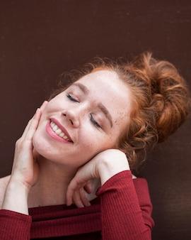 Gros plan belle femme rousse souriante