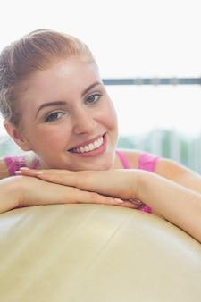 Gros plan d'une belle femme se penchant sur le ballon d'exercice