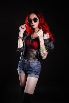 Gros plan d'une belle femme avec tatouage portant des jeans peints courts contre le noir