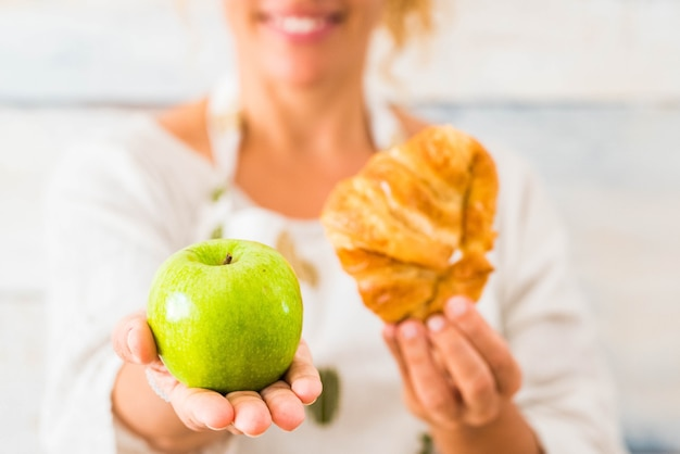 Gros plan sur une belle femme tenant une pomme et un croissant devant la caméra en choisissant entre une vie saine ou un mode de vie malsain - suivre un régime et prendre soin de la nourriture
