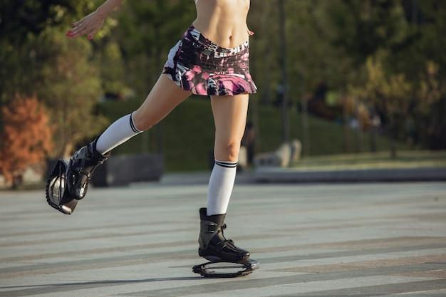 Gros plan belle femme en vêtements de sport sautant dans un kangoo saute des chaussures dans la rue les étés