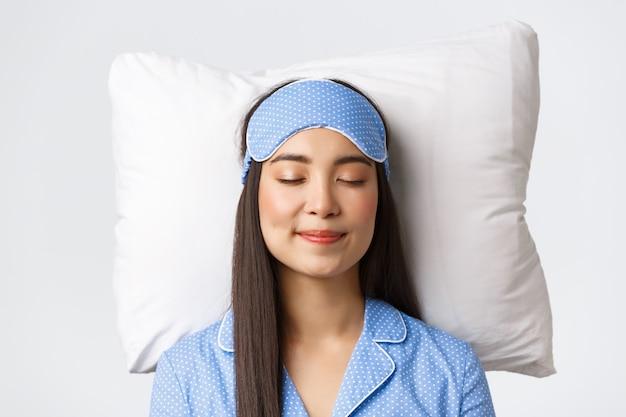 Gros plan d'une belle fille asiatique souriante heureuse en masque de sommeil et pyjama bleu