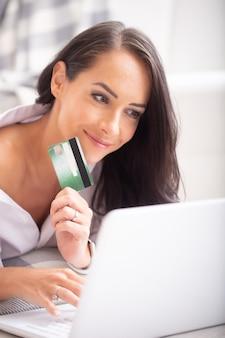 Gros plan d'une belle fille brune souriante dans son ordinateur portable en tapant d'une main et tenant une carte de crédit verte de l'autre.