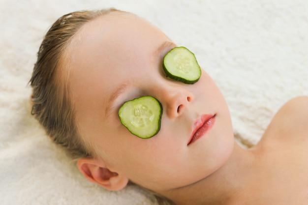 Gros plan d'une belle fille avec un masque facial de concombre