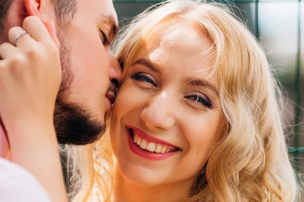 Gros plan d'une belle fille qui embrasse son petit ami par une journée ensoleillée
