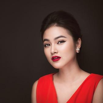 Gros plan d'une belle fille sexy avec un maquillage brillant et des lèvres rouges. femme asiatique de mode de beauté.