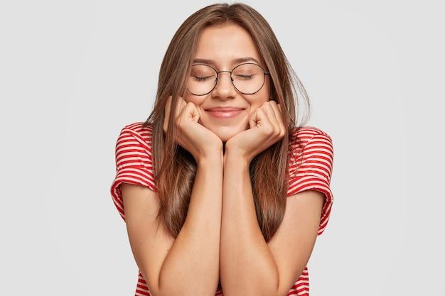 Gros plan de la belle heureuse tient le menton à deux mains, garde les yeux fermés