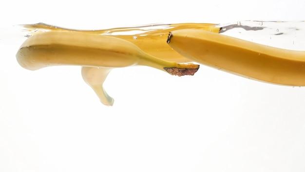Gros plan belle image de bananes tombant dans l'eau claire