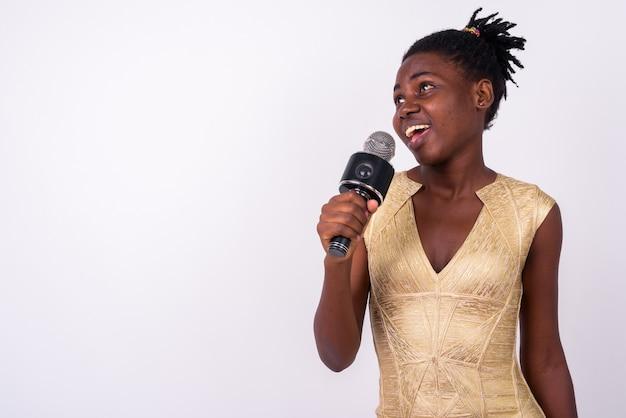 Gros plan de la belle jeune femme africaine vêtue d'une robe or prête à faire la fête isolée
