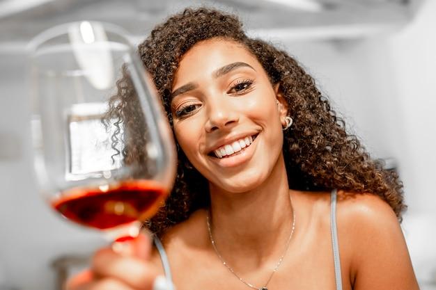 Gros plan sur une belle jeune femme afro-américaine en train de griller en regardant la caméra en simulation de pov de vidéoconférence. nouvelle célébration normale en ligne en raison de la distanciation sociale. fille hispanique noire avec du vin rouge