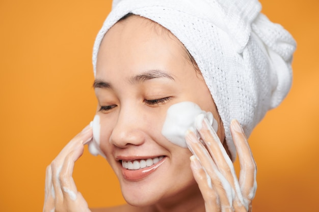 Gros plan sur une belle jeune femme asiatique avec une mousse nettoyante pour les soins de la peau.