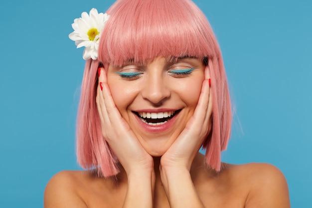 Gros plan de la belle jeune femme aux cheveux rose positive tenant son visage avec les paumes levées tout en souriant agréablement les yeux fermés, debout sur fond bleu