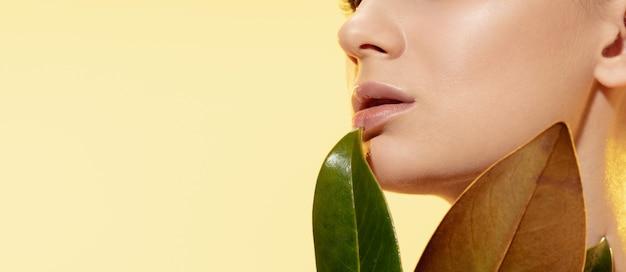 Gros plan d'une belle jeune femme aux feuilles vertes sur fond jaune. concept de cosmétiques, maquillage, traitement naturel et écologique, soins de la peau. peau brillante et saine, mode, soins de santé.