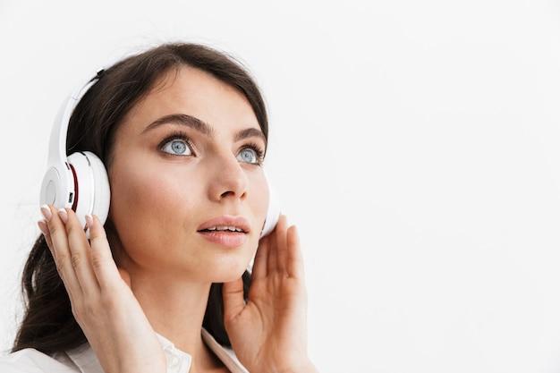 Gros plan d'une belle jeune femme aux longs cheveux bouclés brune vêtue d'une chemise blanche debout isolée sur un mur blanc, appréciant d'écouter de la musique avec des écouteurs
