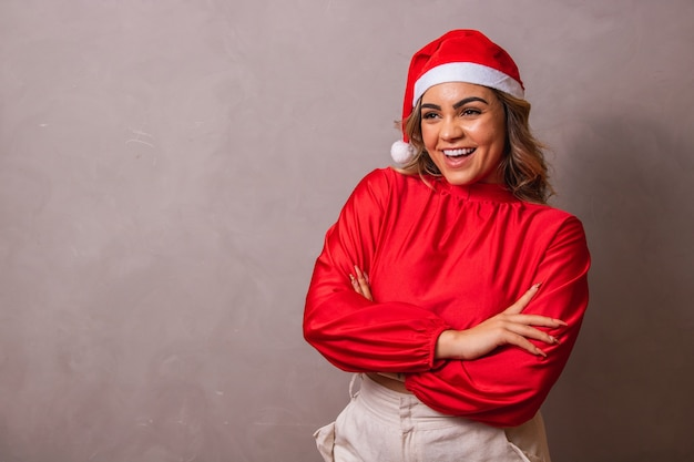 Gros plan d'une belle jeune femme avec bonnet de noel et bras croisés. joyeux noël