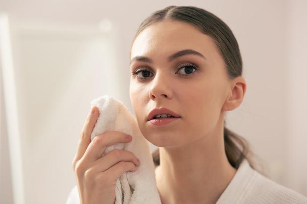 Gros plan d'une belle jeune femme calme debout avec une serviette à la main et la tenant pensivement près de son visage