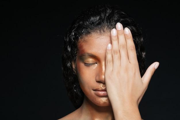 Gros plan de la belle jeune femme a couvert la moitié de son visage à la main sur du noir