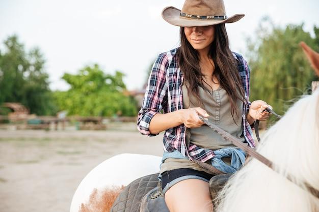 Gros plan de la belle jeune femme cow-girl assise et à cheval dans le village