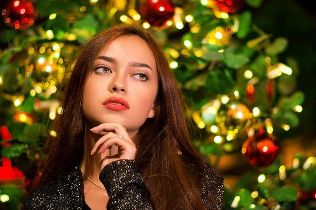Gros plan d'une belle jeune femme devant un arbre de noël