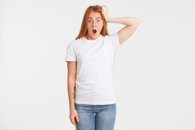 Gros plan d'une belle jeune femme étonnée avec de longs cheveux rouges et des taches de rousseur porte un t-shirt