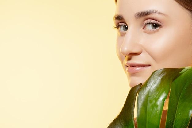 Gros plan de la belle jeune femme avec des feuilles vertes sur blanc