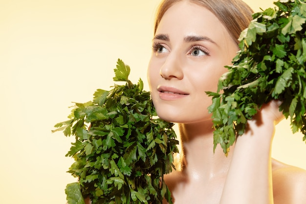 Gros plan de la belle jeune femme avec des feuilles vertes sur fond blanc