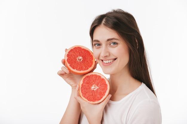 Gros plan d'une belle jeune femme heureuse isolée, montrant des pamplemousses frais en tranches