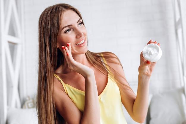 Gros plan d'une belle jeune femme mannequin avec une peau fraîche tenant une bouteille de crème à la main.