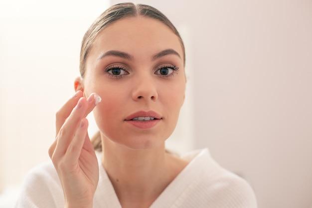 Gros plan sur une belle jeune femme avec un maquillage naturel légèrement souriant tout en essayant une nouvelle crème pour le visage