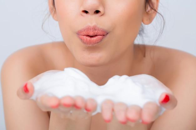 Gros plan d'une belle jeune femme avec une mousse nettoyante pour les soins de la peau