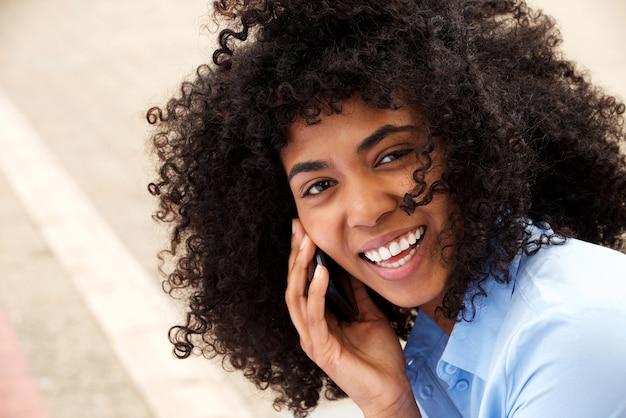 Gros plan belle jeune femme noire parlant sur téléphone portable et en riant