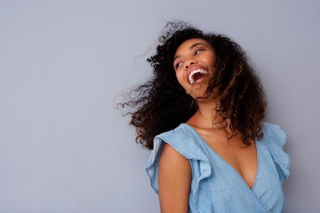Gros plan belle jeune femme noire rire contre le mur gris